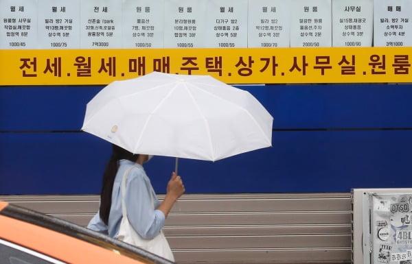 한 시민이 서울 시내 부동산 중개업소 앞을 지나가는 모습. 연합뉴스