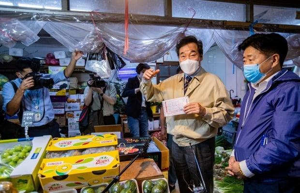 이낙연 더불어민주당 대표가 18일 오후 서울 종로구 통인시장에서 과일을 사고 있다. 사진=뉴스1