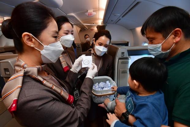 24일 인천공항을 출발한 아시아나항공 'A380 한반도 일주 비행' 항공기에 탑승한 승객이 럭키드로우 행사에서 추첨을 하고 있다. 영종도=공항사진기자단.