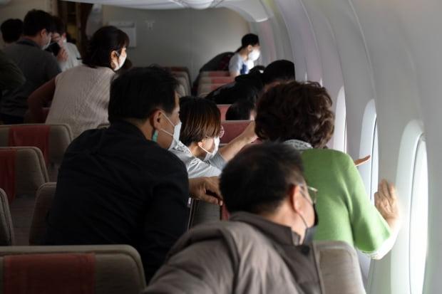 24일 인천공항을 출발한 아시아나항공 'A380 한반도 일주 비행' 항공기에 탑승한 승객들이 바깥 풍경을 보고 있다. 영종도=공항사진기자단