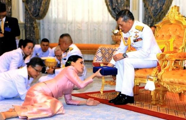 태국 방콕 왕궁에서 열린 마하 와치랄롱꼰 국왕(오른쪽)과 수티다 와찌랄롱꼰 나 아유타야 근위대장의 결혼식 장면. 왕이 바닥에 엎드려 예물을 바친 왕비에게 답례 예물을 건네고 있다. 와치랄롱꼰 왕의 결혼은 이번이 네 번째다. 사진=AP