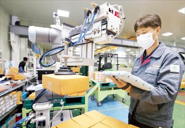 충북 제천의 자동차부품 제조업체 박원 공장에서 한 직원이 KT의 스마트팩토리 협동로봇(코봇)과 함께 작업하고 있다.  KT  제공