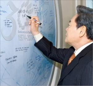 이건희 회장이 2004년 삼성 반도체 사업 30주년을 맞아 '새로운 신화 창조'라는 문구의 기념서명을 하고 있다.
