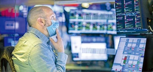 미국과 유럽 등에서 코로나19 재확산으로 경제활동이 위축될 것이란 우려가 커지며 글로벌 증시가 28일 급락했다. 이날 미국 뉴욕증권거래소(NYSE)에서 한 트레이더가 마스크를 쓴 채 심각한 표정으로 시세를 살피고 있다.  /AP연합뉴스