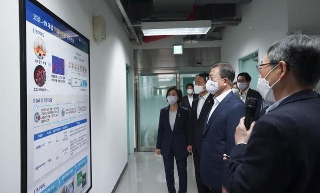 문재인 대통령이 지난 4월 한국파스퇴르연구소를 방문해 코로나19 대응 약물 재창출에 대한 설명을 듣고 있다. / 한경DB