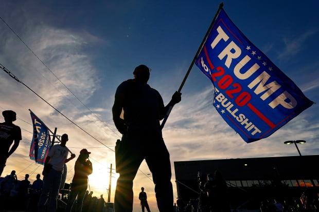 도널드 트럼프 대통령 지지자들이 트럼프 지지 깃발을 들고 서 있다. 사진=피닉스 AP/연합뉴스