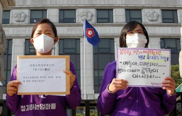정치하는엄마들 활동가들이 16일 오전 서울 종로구 헌법재판소 앞에서 열린 '공무원 3년·비공무원 1년, 육아휴직 차별에 대한 평등권·양육권 침해 헌법소원심판청구 기자회견'에서 피켓을 들고 있다.  뉴스1