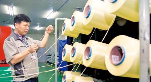 코오롱인더스트리 구미공장에서 한 직원이 아라미드 제품을 점검하고 있다.  코오롱 제공