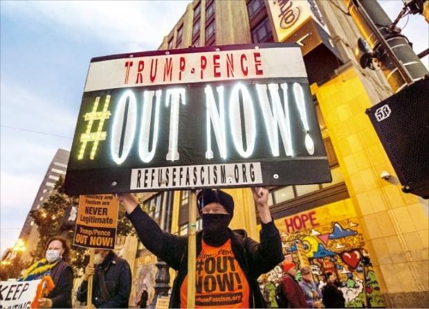 """< """"트럼프 아웃"""" > 조 바이든 미국 민주당 대선 후보 지지자들이 5일(현지시간) 캘리포니아주 샌프란시스코에 있는 소셜미디어 업체 트위터 본사 앞에서 시위를 벌이고 있다.  /AP연합뉴스"""