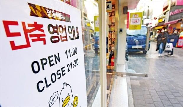 < 썰렁한 명동 거리 > 24일 수도권 지역에 사회적 거리두기 2단계 조치가 시행된다. 이번 조치로 다음달 7일 밤 12시까지 수도권 내 카페는 포장·배달 영업만 가능하고, 일반음식점은 오후 9시 이후 홀 영업이 중단된다. 거리두기 2단계를 하루 앞둔 23일 서울 명동 거리의 한 상점 앞에 영업 단축을 알리는 안내문이 붙어 있다. 신경훈 기자 khshin@hankyung.com