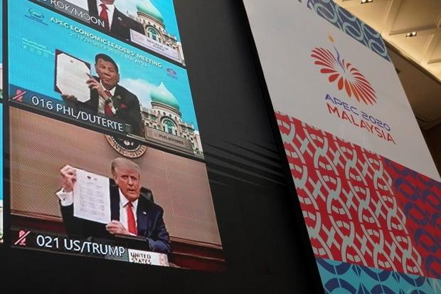 도널드 트럼프 미국 대통령이 20일 열린 아시아태평양경제협력체(APEC) 화상 정상회의에서 다른 참가국 지도자들과 함께 '정상선언문'을 들고 있는 모습이 화면에 비치고 있다. 사진=AP