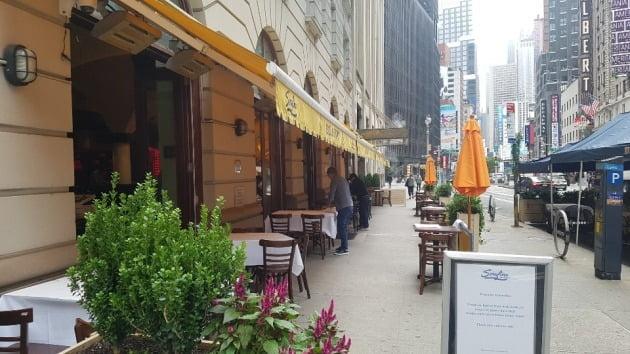 최근 뉴욕 맨해튼에서 한 식당 종업원들이 손님이 없어 썰렁한 가운데 야외 테이블을 정리하고 있다. 뉴욕=조재길 특파원