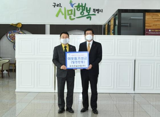 요진건설산업 이병호 상무(오른쪽)가 안승남 구리시장(오른쪽)에게 이웃 돕기 성금을 전달하고 있다. /요진건설산업 제공