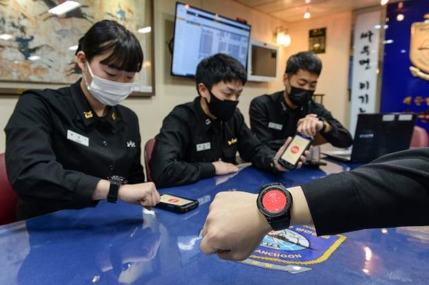 지난 11일 해군 1함대 양만춘함 승조원들이 사관실에서 스마트워치와 단말기를 이용해 전투배치 상황을 확인하고 있는 모습. 해군 제공