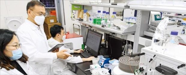 이성욱 단국대 생명융합학과 교수 겸 알지노믹스 대표(가운데)가 지난 4일 경기 성남 판교 알지노믹스 연구실에서 리보핵산(RNA) 치환 플랫폼 기술 기반의 진행성 간암(HCC) 타깃 치료물질에 대한 연구 결과를 두고 연구원들과 의논하고 있다.  강은구 기자 egkang@hankyung.com