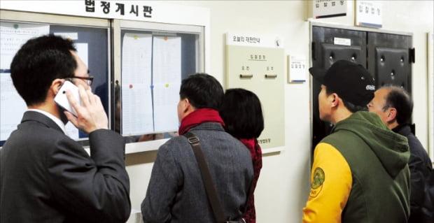 경매 투자자들이 서울동부지방법원 게시판에 나온 매물 정보를 살펴보고 있다. 한경DB