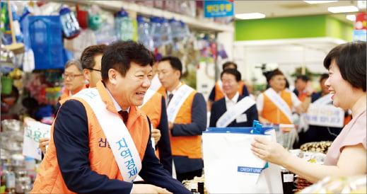 김윤식 신협중앙회장(왼쪽)과 신협 임직원들이 지난해 고용산업위기지역으로 선포된 전북 군산을 찾아 지역경제 살리기 캠페인에 나섰다.    신협중앙회 제공