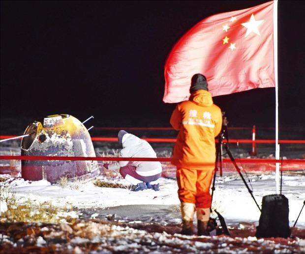 중국 국가항천국 직원이 17일 새벽 눈 덮인 초원에 착륙한 창어 5호의 캡슐에 접근해 작업하고 있다. /신화연합뉴스