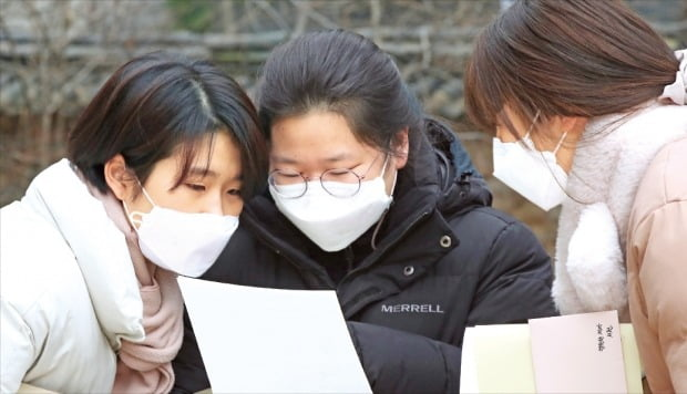 < 인생 최대 떨리는 순간 >  2021학년도 대학수학능력시험 성적표가 23일 수험생들에게 배부됐다. 코로나19 확산 예방을 위해 이날 현장 배포는 학생이 성적표만 받고 나가는 '워킹 스루', 차량을 이용한 '드라이브 스루' 등의 방식으로 이뤄졌다. 서울 정동 이화여고에서 학생들이 성적표를 확인하고 있다.  /사진공동취재단