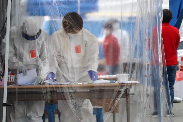 지난 11일 대구 수성구보건소 선별진료소에서 의료진이 코로나19 검사를 위해 바쁘게 움직이고 있다. 사진 = 뉴스1