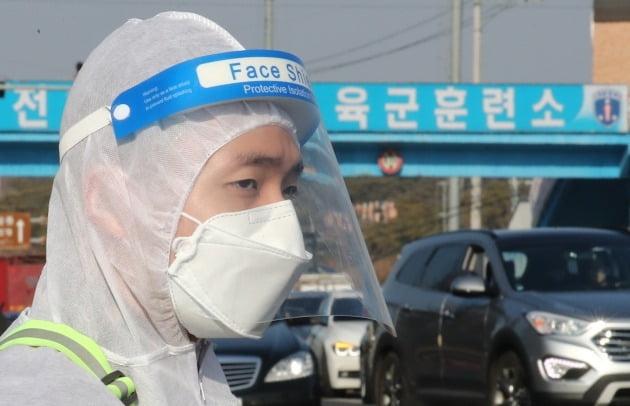 지난달 28일 충남 논산훈련소 입영심사대 정문에서 방호복을 입은 군장병이 입영장병을 안내하고 있는 모습. 뉴스1