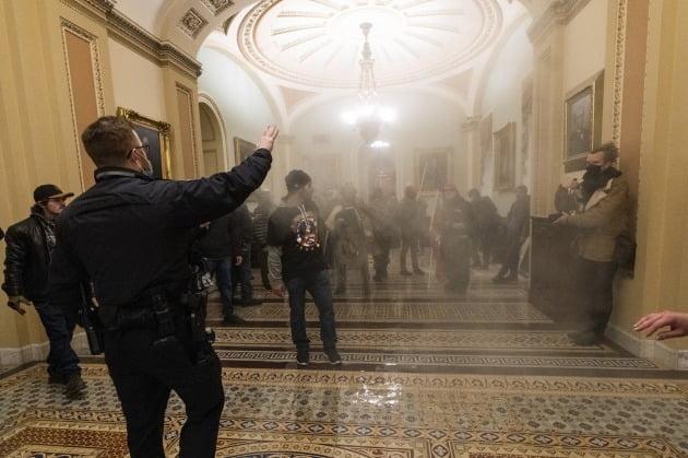 지난 6일(현지시간) 친트럼프 시위대가 난입한 의사당 내부. 최루가스 연기가 자욱하다. AP연합뉴스