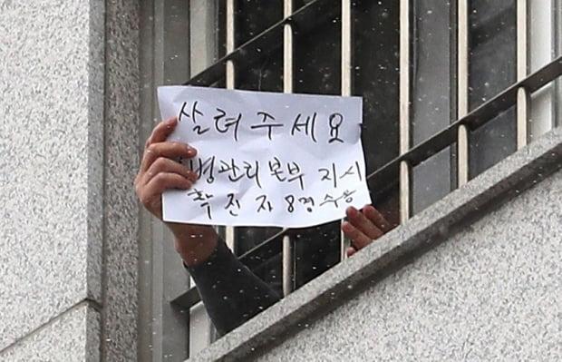 서울 송파구 동부구치소에서 한 수용자가 자필로 '살려주세요'라고 쓴 문구를 취재진에게 보여주고 있다. 사진=뉴스1