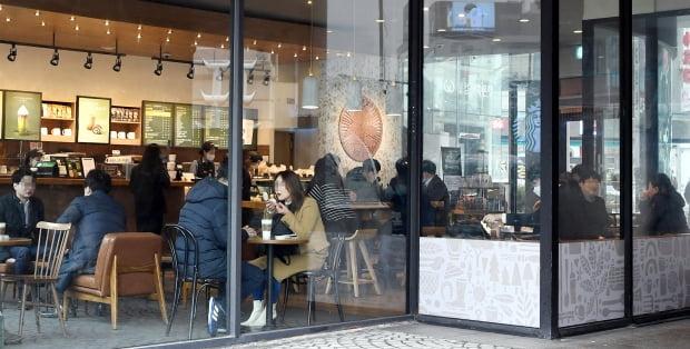18일 카페, 헬스장, 노래방 등 다중이용시설에 대한 방역조치가 일부 완화됐다. 이날 서울 명동의 한 프랜차이즈 카페에서 시민들이 커피를 마시고 있다. 카페는 오후 9시까지 매장 내 취식이 허용된다. 허문찬기자 sweat@hankyung.com