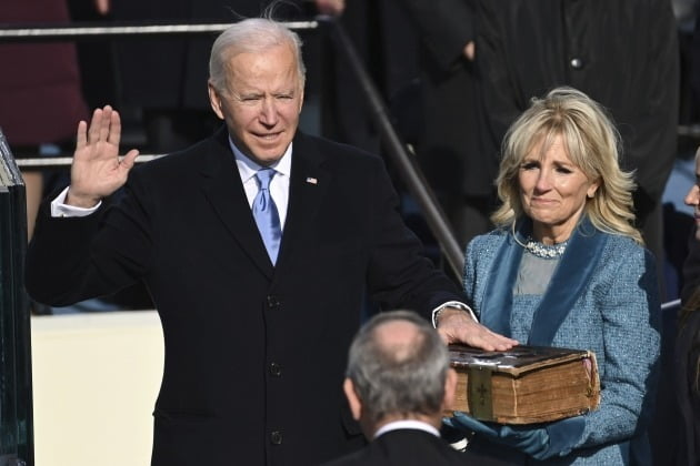 조 바이든 미국 대통령(왼쪽)이 20일(현지시간) 워싱턴DC의 연방의회 의사당에서 열린 취임식에서 존 로버츠 연방대법원장을 앞에 두고 선서를 하고 있다. / 워싱턴 AP=연합뉴스