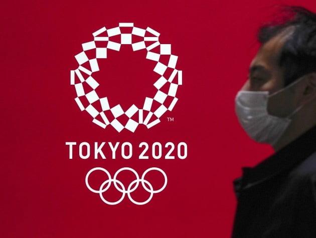 도쿄올림픽 로고 앞으로 마스크를 착용한 도쿄 시민이 지나가고 있다. [사진=EPA 연합뉴스]