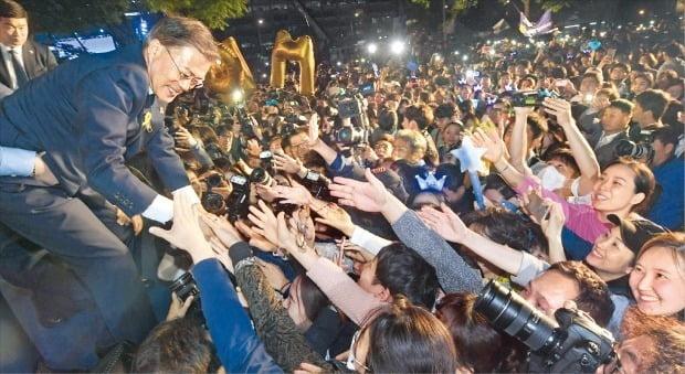문재인 대통령이 2017년 대선에서 승리한 후 지지자들의 손을 잡아주고 있다. 신경훈 기자 khshin@hankyung.com