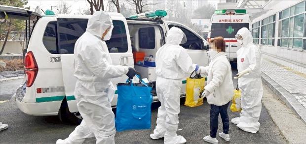 < 코로나 환자 짐 나눠들고… > 코로나19 전담 병원인 서울시립서북병원은 병원장부터 미화직원까지 병원 가족 450여 명이 바이러스에 맞서 싸우고 있다. 지난달 30일 이송된 확진자의 짐을 간호사들이 나눠 들고 있다.   /김영우  기자  youngwoo@hankyung.com