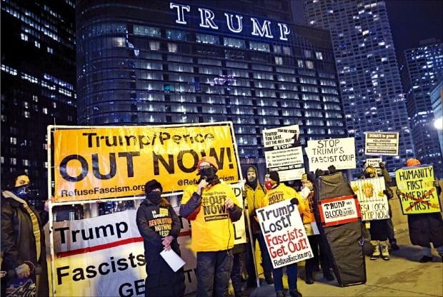 도널드 트럼프 미국 대통령의 퇴진을 촉구하는 시위대가 7일(현지시간) 일리노이주 시카고의 트럼프타워 앞에서 농성을 벌이고 있다. 시위대가 든 손팻말에는 '트럼프는 졌다. 파시스트는 물러나라'는 문구가 적혀 있다.  /APF연합뉴스