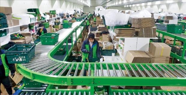 오아시스의 경기 성남 본사 물류센터에서 작업자들이 모바일 앱으로 고객 주문 물품을 확인하며 포장 작업을 하고 있다. 약 400명의 물류시설 근로자들은 100% 정규직 사원이다. 오아시스  제공