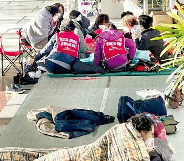 < 방역지침도 무시한채… > 전직 LG트윈타워 청소근로자들이 지난달부터 서울 여의도 LG트윈타워 1층 로비를 점거한 채 농성을 이어가고 있다. 이들은 LG 측의 계약해지로 일자리를 잃었다며 70세까지 이곳에서 근무할 수 있도록 해달라고 요구하고 있다.  독자 제공