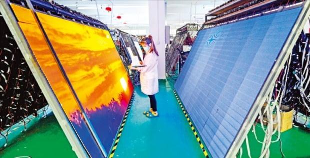 반도체, LCD·OLED 패널, MLCC 등 주요 전자부품 생산량이 수요를 못 따라가는 '공급 부족' 현상이 확산하고 있다. 사진은 중국 선전에 있는 한 디스플레이업체 직원이 LED 패널을 검사하고 있는 모습.  /연합뉴스