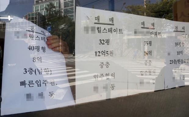 서울의 한 부동산중개업소에서 관계자가 계약된 전세 물건이 표시된 안내문을 떼고 있다. /연합뉴스