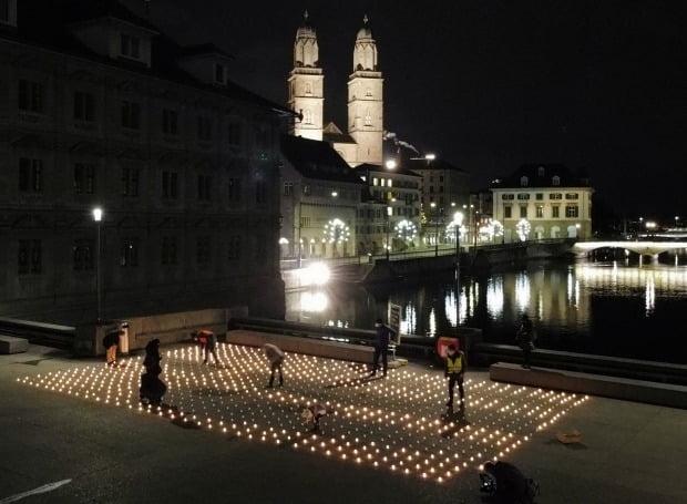 지난해 말 스위스 취리히 다리 위에서 시민들이 코로나19 희생자 추모 집회를 위해 촛불을 켜고 있다. /사진=로이터