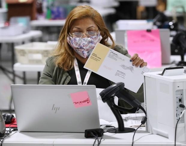 5일(현지시간) 미국 조지아주 로렌스빌의 선거관리소 직원이 조지아주 연방 상원의원 결선 부재자 투표지를 확인ㆍ분류하는 절차를 진행하고 있다. 사진=AP