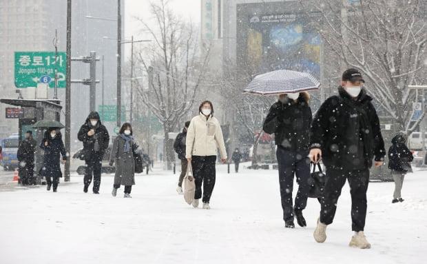 눈이 내리는 18일 오전 서울 광화문광장 인근에서 시민들이 눈을 맞으며 걸어가고 있다. /사진=연합뉴스