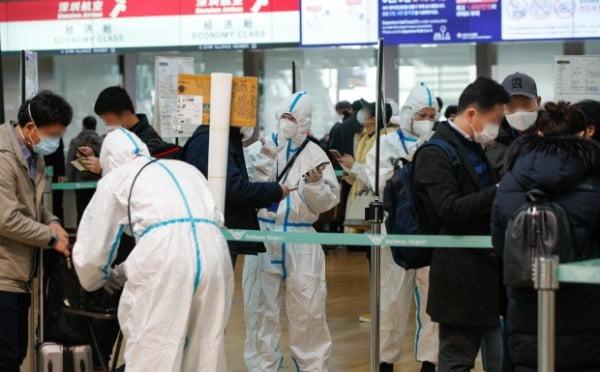 국내 신종 코로나바이러스 감염증(코로나19) 확진자가 처음 발생한 지 1년째 되는 날인 지난 20일 인천국제공항 1터미널 출국장에서 방역복을 입은 항공사 관계자들이 탑승객을 안내하고 있다. /사진=뉴스1