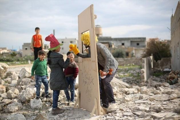 세계 포트폴리오 '사람' 부문 - 무네브 타임, 시리아 / 국제 연극의 날을 맞아 연극예술가 왈리드(Walid)가 아이들을 위해 인형극을 공연하는 모습. 그는 2013년부터 난민촌을 순회하며 시리아 어린이들을 위한 인형극과 그림자극을 공연하고 있다.