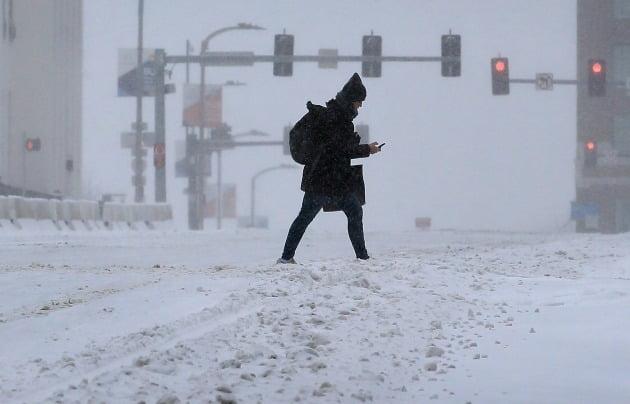 15일(현지시간) 미국 미주리주 세인트루이스에서 폭설이 내린 시내를 한 시민이 걷고 있다. 미 기상청은 북부의 메인주에서 남부의 텍사스주까지 25개 주에 겨울 폭풍 경보 등을 발령했으며 최소 1억5천만 명이 한파의 영향을 받을 것으로 예보했다. [사진=AP 연합뉴스]