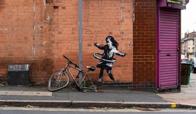 뱅크시가 노팅엄의 한 건물에 그린 '훌라후프를 하는 소녀' [사진=뱅크시 공식 홈페이지 캡처]