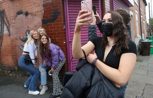 뱅크시가 노팅엄의 한 건물에 그린 '훌라후프를 하는 소녀' 앞에서 기념 사진을 촬영 중인 현지 젊은이들 [사진=로이터 연합뉴스]