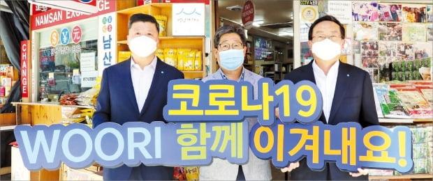 손태승 우리금융그룹 회장(오른쪽)과 권광석 우리은행장(왼쪽)이 서울 남대문시장을 찾아 코로나19 위기 극복을 응원하고 있다.  우리은행 제공