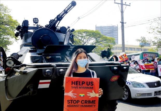 미얀마 최대 도시인 양곤에서 15일 벌어진 군부 쿠데타 항의 시위에 참여한 한 여성이 장갑차 앞에서 '우리를 도와 미얀마를 지켜달라, 인권을 억압하는 범죄를 멈춰라'고 적힌 팻말을 들고 있다. 지난 1일 쿠데타를 일으킨 미얀마 군부는 양곤 시내 곳곳에 장갑차와 군 병력을 배치했다.  EPA연합뉴스