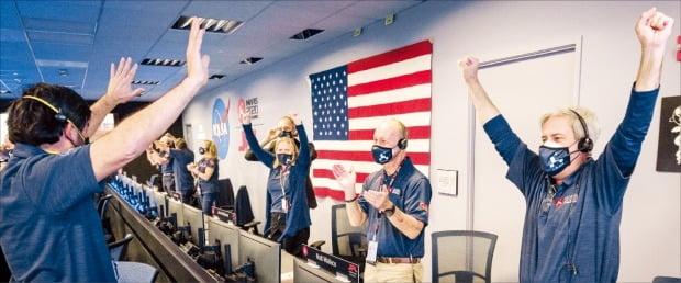 < 환호하는 NASA > 미 항공우주국(NASA)의 퍼시비어런스 팀원들이 18일(현지시간) NASA의 제트추진연구소 관제센터에서 퍼시비어런스의 착륙 소식을 듣고 환호하고 있다.  /로이터연합뉴스