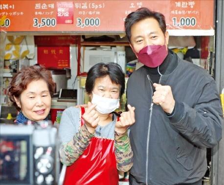 오세훈 국민의힘 서울시장 예비후보(오른쪽)가 21일 서울 대현동 이화여대 인근 상가에서 상인들과 사진을 찍고 있다.   국회사진기자단