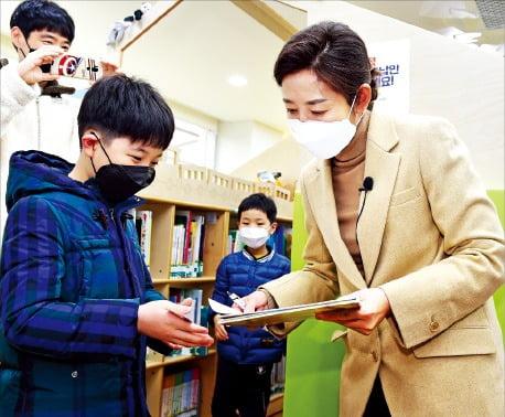 나경원 국민의힘 서울시장 예비후보(오른쪽)가 21일 서울 중계동 노원어린이도서관에서 한 어린이에게 사인을 해주고 있다. 국회사진기자단